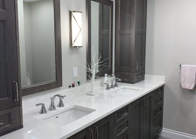 Grey custom cabinets-framed mirrors-undermount sinks-furniture cabinets